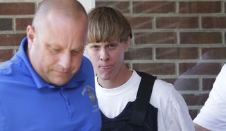 FILE - In this June 18, 2015 file photo, Charleston, S.C., shooting suspect Dylann Storm Roof, center, is escorted from the Sheby Police Department in Shelby, N.C. Roof is accused of killing nine people inside Emanuel African Methodist Episcopal Church in Charleston on June 17. (AP Photo/Chuck Burton)