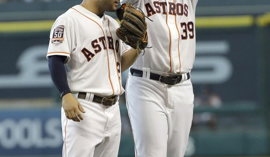 Houston Astros second baseman Jose Altuve (27) talks with starting pitcher Brett Oberholtzer (39) during the first inning of a baseball game Saturday, June 27, 2015, in Houston. The Yankees scored four runs on a Brian McCann grand slam in the inning. (AP Photo/David J. Phillip)