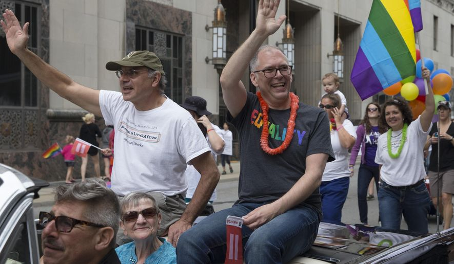 Gay marriage plaintiff James Obergefell, center, waves during the Cincinnati Pride parade, Saturday, June 27, 2015, in Cincinnati. On Friday, the U.S. Supreme Court ruled that same-sex couples have the right to marry nationwide. (AP Photo/John Minchillo) (AP Photo/John Minchillo)