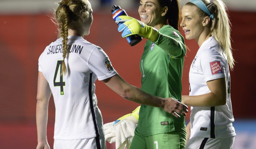 U.S. goalie Hope Solo and teammates Julie Johnston (19) and Becky Sauerbrunn (4) celebrate the team's win over China in a quarterfinal match in the FIFA Women's World Cup soccer tournament, Friday, June 26, 2015, in Ottawa, Ontario, Canada. (Adrian Wyld/The Canadian Press via AP)
