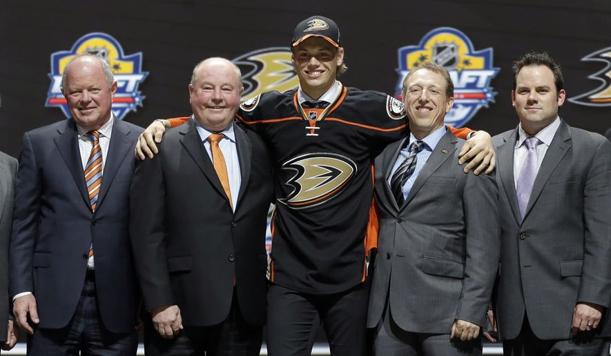Jacob Larsson, of Sweden, center, poses with Anaheim Ducks executives after being chosen 27th overall during the first round of the NHL hockey draft, Friday, June 26, 2015, in Sunrise, Fla. (AP Photo/Alan Diaz)