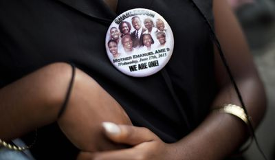 Krislynn Rambert, of Charleston, S.C., wears a button in memory of the victims of last week's mass shooting while waiting on line to enter Sen. Clementa Pinckney's funeral service, Friday, June 26, 2015, in Charleston, S.C. President Barack Obama will deliver the eulogy at Pinckney's funeral at a nearby college arena. (AP Photo/David Goldman)