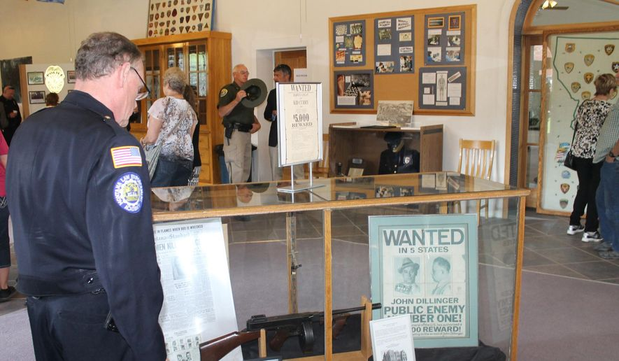In this Tuesday, June 23, 2015, photo, Butte District Court Bailiff Dan Hollis looks at a machine gun and authentic John Dillinger wanted poster from the early 1930s on display at the grand opening of the Montana Law Enforcement Museum in Philipsburg, Mont. (Mike Smith/The Montana Standard via AP)