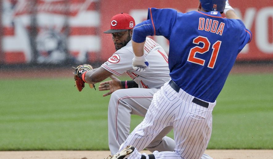 Cincinnati Reds second baseman Brandon Phillips, left, tags out New York Mets' Lucas Duda who was trying to reach second base during the seventh inning of Saturday's suspended baseball game at Citi Field, Sunday, June 28, 2015, in New York. (AP Photo/Seth Wenig)