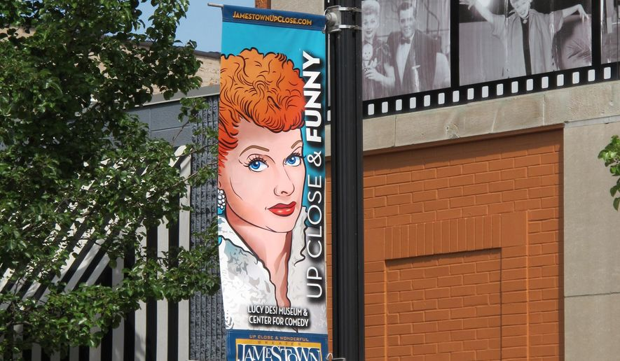 In this June 26, 2015 photo, a banner hangs outside the Lucille Ball-Desi Arnaz Museum in Ball's hometown of Jamestown, N.Y. The nonprofit National Comedy Center Inc., which runs the museum, plans to break ground this summer on the National Comedy Center to be located nearby. The national center will explore the art and science of comedy across all platforms and generations. (AP Photo/Carolyn Thompson)