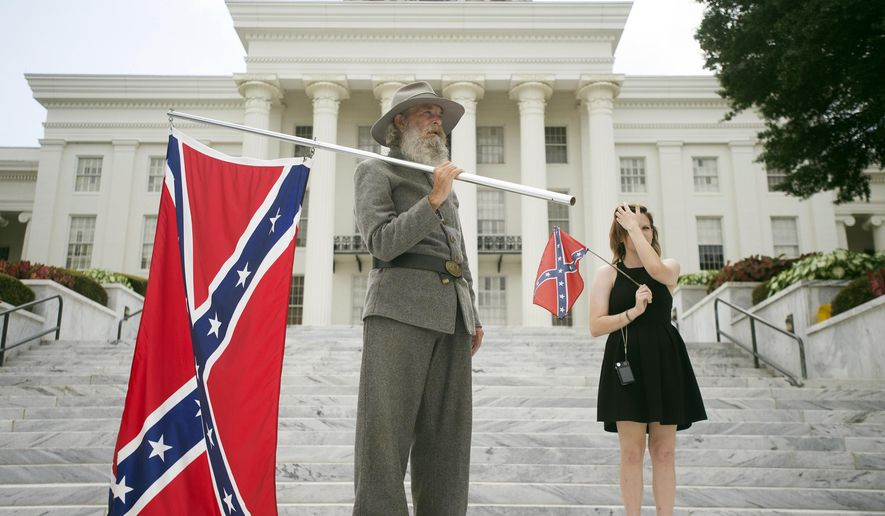 FILE - In this Saturday, June 27, 2015 file photo, Dan Williams, 65, of Ashville, Ala., holds a Confederate flag while standing with his daughter Bonnie-Blue Williams, 15, in front of the Alabama State Capitol building during a Confederate flag rally in Montgomery, Ala. Across the South, Confederate symbols are toppling or teetering or at least getting critical new looks. But is it a sign of real change in a region known for defending its complex traditions, or simply the work of frightened politicians and nervous corporate bean counters scrambling for cover in the wake of another white-on-black atrocity? (Albert Cesare/The Montgomery Advertiser via AP, File)  NO SALES; MANDATORY CREDIT: ALBERT CESARE/THE MONTGOMERY ADVERTISER