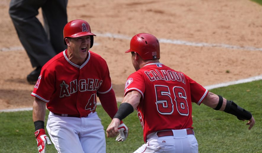 Los Angeles Angels' Daniel Robertson, left, celebrates with teammate Kole Calhoun after Calhoun scored a baseball game-winning run on a wild pitch during the 10th inning against the Seattle Mariners, Sunday, June 28, 2015, in Anaheim, Calif. (AP Photo/Mark J. Terrill)