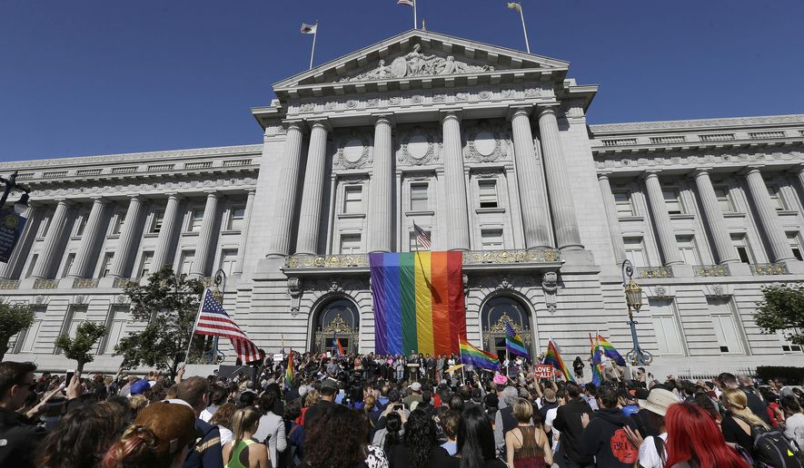 FILE - In this June 26, 2015, file photo, a crowd gathers as San Francisco Mayor Ed Lee speaks at a news conference outside of City Hall in San Francisco, after the U.S. Supreme Court ruled that  same-sex couples have the right to marry nationwide. Rainbows and good cheer will be out in force this weekend as hundreds of thousands of people pack gay pride events from New York to Seattle, San Francisco to Chicago to celebrate the Supreme Court ruling legalizing same-sex marriage. (AP Photo/Jeff Chiu, File)