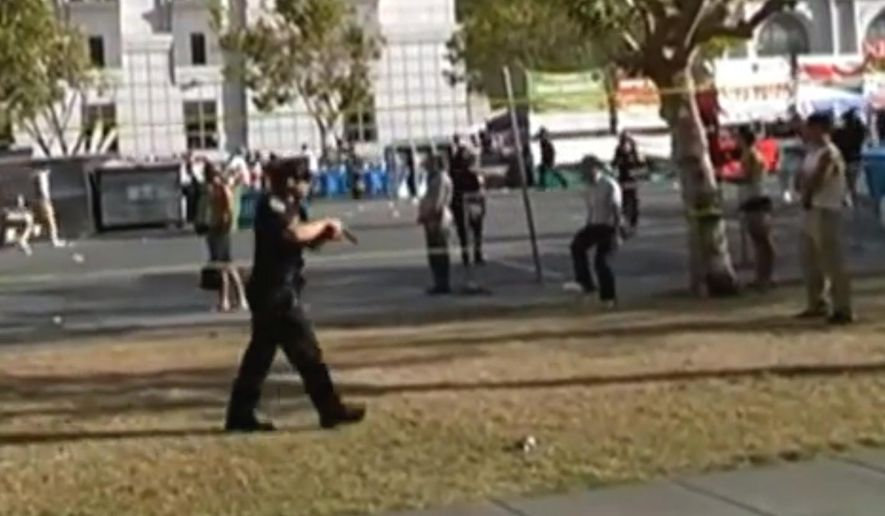 In this image taken from video provided by Sean-Franc Strang, a police officer has his gun drawn after shots were fired at a gay pride event in San Francisco, Saturday, June 27, 2015. Police say a bystander was shot at a gay pride event in San Francisco's Civic Center when an argument between several young men turned violent. Officer Carlos Manfredi says several people were detained for questioning after the shooting occurred around 6 p.m. Saturday. (Sean-Franc Strang via AP)