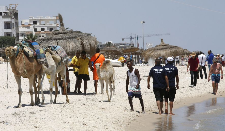Police officers patrol on the beach of  Sousse, Tunisia, Sunday, June 28, 2015. Tunisia's top security official says 1,000 extra police are being deployed at tourist sites and beaches in the North African nation after Friday's attack. (AP Photo/Abdeljalil Bounhar)