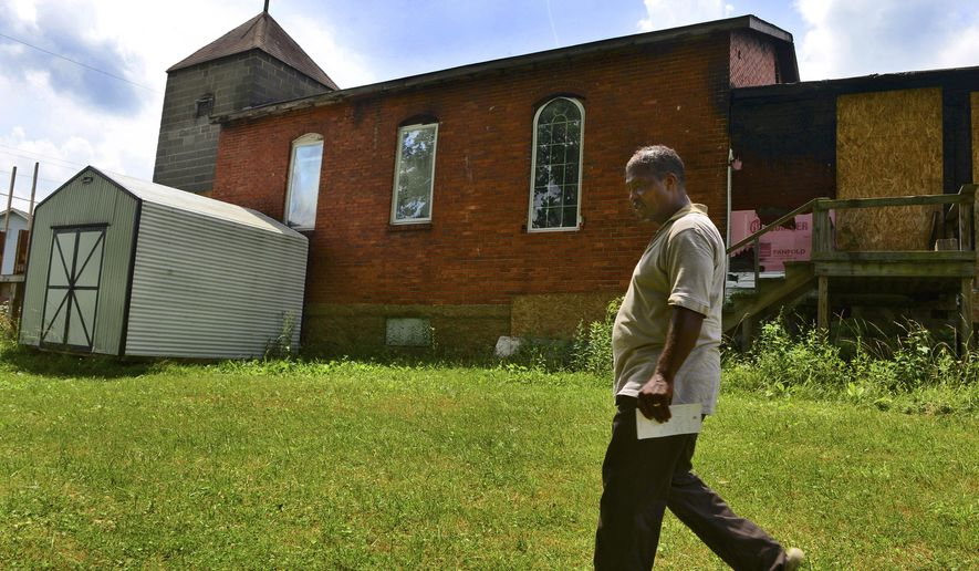 ADVANCE FOR MONDAY JUNE 29 AND THEREAFTER This Thursday June 18, 2015 image, Dimetrius Watson walks the grounds of the Church of Deliverance United Holy Church in Saint Albans, W.Va.  The smoke-charred brick and cinder block which burns in January stands abandoned and forlorn on Mary Street, where it has been a landmark for more than 100 years.  (Kenny Kemp/Charleston Gazette via AP)