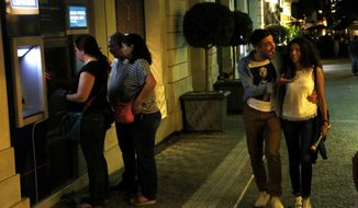A couple passes by the ATM machines used by people in Monastiraki in Athens, early Monday, June 29, 2015.   Greece's five-year financial crisis took its most dramatic turn to date Sunday, with Prime Minister Alexis Tsipras announcing Greek banks would remain shut indefinitely and restrictions would be imposed on cash withdrawals. (AP Photo/Petros Karadjias)