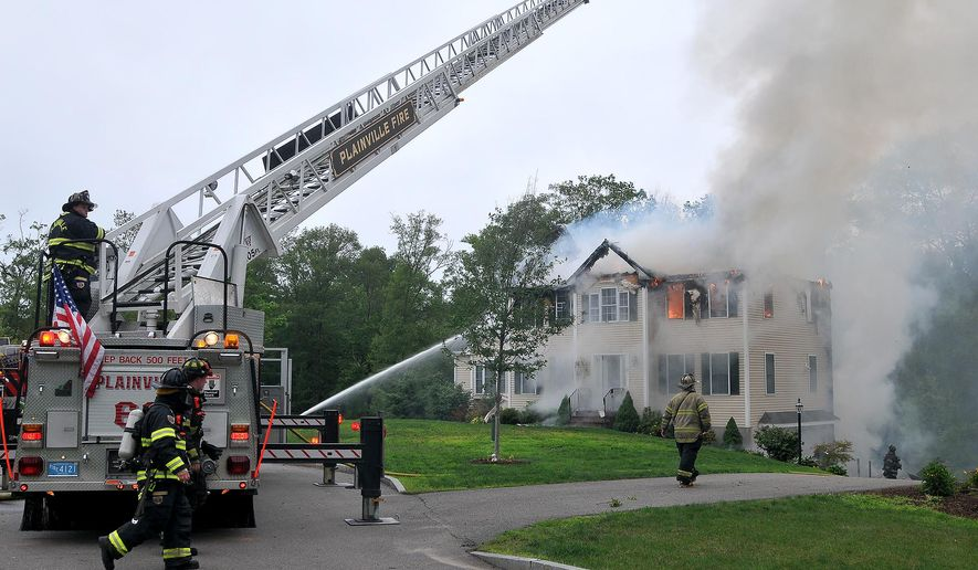Firefighters work to extinguish flames after a small plane crashed into a house on Sunday in Plainville, Mass. (Associated Press)