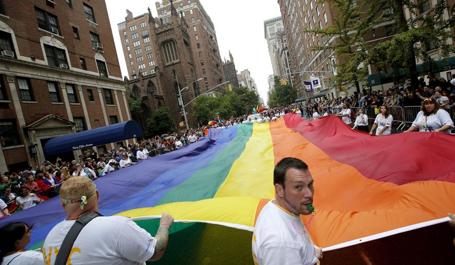 Participants carry a rainbow-colored flag down Fifth Avenue in New York during the Heritage Pride March, Sunday, June 28, 2015. A large turnout was expected for gay pride parades across the U.S. following the landmark Supreme Court ruling that said gay couples can marry anywhere in the country. (AP Photo/Kathy Willens)