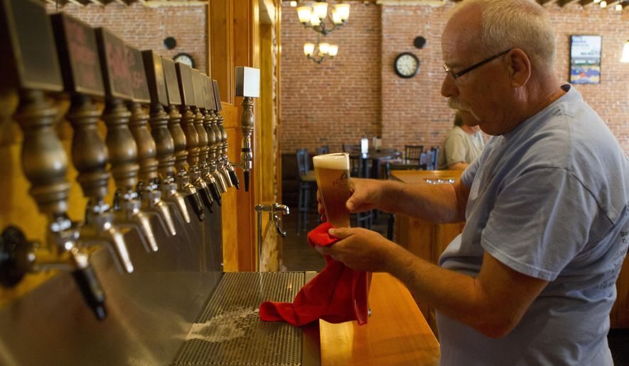 ADVANCE FOR USE SUNDAY, JUNE 28, 2015, AND THEREAFTER- In this June 19, 2015 photo, Bartender Tom Dahl serves a beer at Franklin Street Brewing Co. in Manchester, Iowa. More than two dozen styles of beer have flowed through the tap handles of Franklin Street Brewing Co. since brothers Chad and Kyle Sands opened the doors of the production brewery in April 2014. (Jake Crandall/Telegraph Herald via AP)