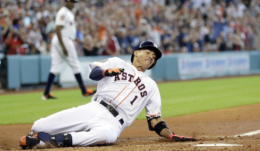 Houston Astros' Carlos Correa (1) slides across home plate to score after hitting a double and advancing to home on a fielding error by New York Yankees left fielder Brett Gardner during the fourth inning of a baseball game Sunday, June 28, 2015, in Houston. (AP Photo/David J. Phillip)