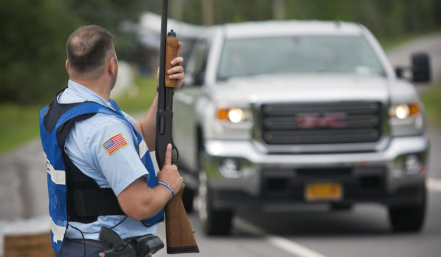 A New York State corrections officer holds a weapon at a checkpoint along State Route 30 at the intersection with Travers Rd. in the town of Malone, N.Y. on Saturday, June 27, 2015 as the search for escaped prisoner David Sweat continues. (Jason Hunter/Watertown Daily Times via AP)