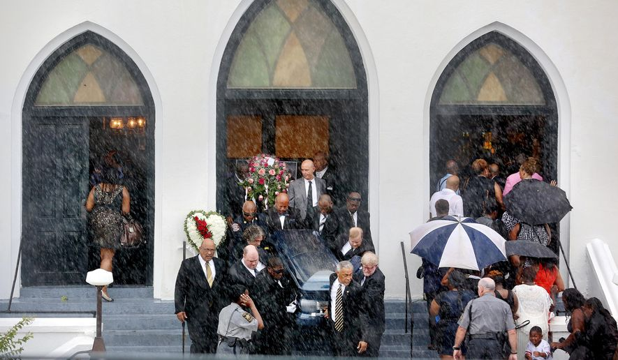 Rain falls as pallbearers exit Emanuel AME Church carrying the casket of Cynthia Hurd as mourners for Susie Jackson and Tywanza Sanders file inside the church for their funerals Saturday, June 27, 2015, in Charleston, S.C. Hurd, Jackson and Sanders were three of the nine people killed in the shooting at the church on June 17. (Grace Beahm/The Post And Courier via AP) ** FILE **