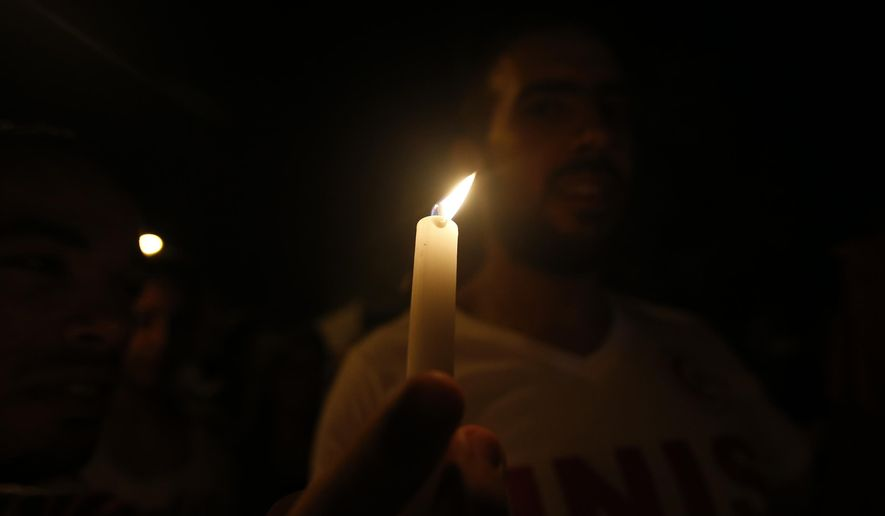 A man holds a candle during a protest against terrorism in Sousse, Tunisia, Saturday, June 27, 2015. The morning after a lone gunman killed at tens of people at a beach resort in Tunisia, busloads of tourists are heading to the nearby Enfidha-Hammamet airport hoping to return to their home countries. (AP Photo/Darko Vojinovic)