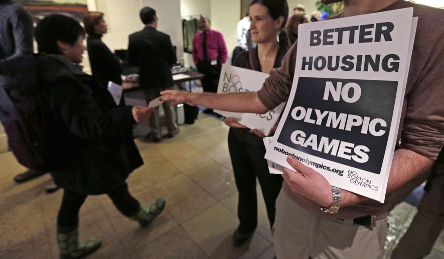 FILE - In this Feb. 5, 2015, file photo, Jonathan Cohn, of the Fenway neighborhood of Boston, hands out fliers while standing with Claire Blechman, of Somerville, Mass., prior to the first public forum regarding the Boston 2024 Olympic bid, in Boston. While Bostonians are hesitant to host the Olympics, Americans across the country overwhelmingly support the idea of the games on home turf, according to a new Associated Press-GfK poll. The support decreases when people are asked if they would want the Olympics in their local area. It dips even further when they are asked if public funds should be used to pay for them. (AP Photo/Charles Krupa, File)