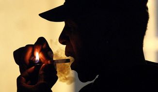 This May 5, 2011, file photo shows a unidentified man smoking medical marijuana during karaoke night at the Cannabis Cafe, in Portland, Ore.  (AP Photo/Rick Bowmer, File)