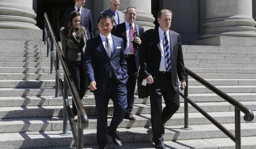 Benjamin Wey, CEO of New York Global Group, bottom left, leaves Manhattan Federal Court Wednesday, June 24, 2015, in New York. On Friday, June 26, a jury began deliberating in an $850 million lawsuit brought by a young woman who worked for Wey. Hanna Bouveng claims Benjamin Wey used his power as owner of New York Global Group to coerce her into four sexual encounters before firing her after discovering she had a boyfriend. She says he then launched a smear campaign through the Internet, depicting her falsely as a prostitute, extortionist or drug user, and wrote vicious emails to her friends and family.  (AP Photo/Frank Franklin II)