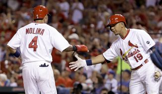 St. Louis Cardinals' Yadier Molina, left, is congratulated by teammate Jon Jay after scoring on a single by Xavier Scruggs during the second inning of a baseball game against the Chicago Cubs Sunday, June 28, 2015, in St. Louis. (AP Photo/Jeff Roberson)