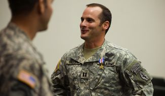 In this Jan. 4, 2011 file photo, U.S Army Capt. Mathew Golsteyn, right, is congratulated by fellow soldiers following the Valor Awards ceremony for 3rd Special Forces Group at Fort Bragg, N.C. Golsteyn, who was accused of tracking down and killing an unarmed bomb-making suspect in Afghanistan, is being recommended for an honorable discharge even though the military panel that looked into the case determined his conduct was unbecoming an officer. The Fort Bragg panel reached the finding late Sunday, June 28, 2015. (James Robinson/The Fayetteville Observer via AP)