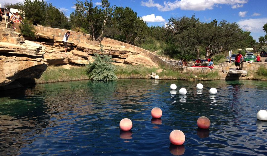 "This Saturday, June 6, 2015 photo shows a boy leaping into the water at Blue Hole State Park in Santa Rosa, N.M. Blue Hole is part of the New Mexico Tourism Department's ""New Mexico True"" campaign, an effort aimed at drawing more tourists to the state. Gov. Susana Martinez on Monday, June 29, 2015, announced statewide visitor numbers for 2014 marked another record-breaking year. (AP Photo/Susan Montoya Bryan)"