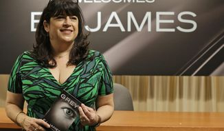 """FILE - In this Thursday, June 18, 2015 file photo, author EL James poses for photographers before signing her new book, """"Grey,"""" at a Barnes and Noble bookstore in New York. The hashtag """"AskELJames"""" trended nationwide as the """"Fifty Shades of Grey"""" writer took questions online. (AP Photo/Mary Altaffer, File)"""