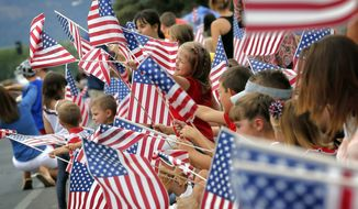 People wave flags as the Independence Day parade rolls down Main Street on July 4, 2014 in Eagar, Ariz. (Associated Press)