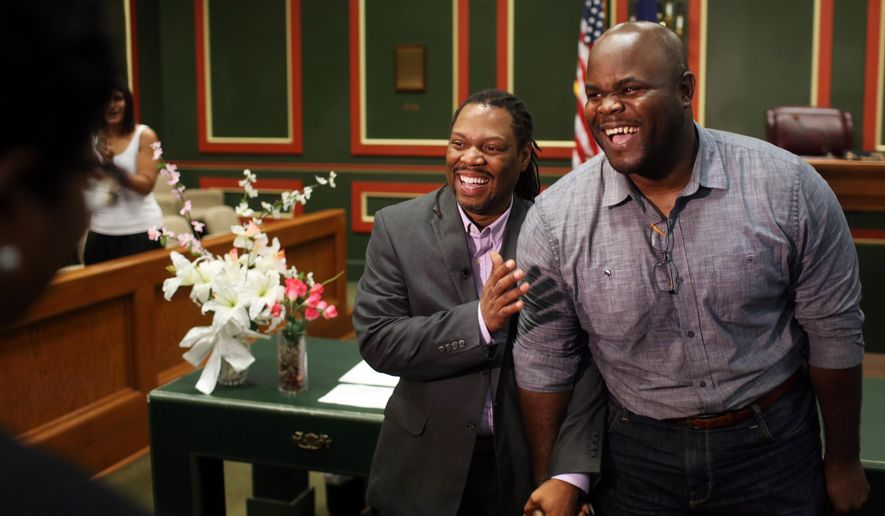 Michael Robinson, left, and Earl Benjamin, partners for almost 14 years, exchange vows before Judge Paula Brown in a ceremony at Orleans Parish Civil District Court on Monday, June 29, 2015, in New Orleans. Court clerks across the state of Louisiana received the go-ahead to issue same-sex marriage licenses Monday. (Kathleen Flynn/NOLA.com The Times-Picayune via AP)