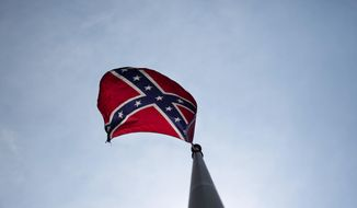 """A Confederate flag flies at the base of Stone Mountain Tuesday, June 30, 2015, in Stone Mountain, Ga. At Georgia's iconic Stone Mountain - where the Confederacy is enshrined in a giant bas-relief sculpture, the Ku Klux Klan once held notorious cross-burnings and rebel battle flags still wave prominently, officials are considering what to do about those flags. The park, which now offers family-friendly fireworks and laser light shows, is readying its """"Fantastic Fourth Celebration"""" Thursday through Sunday, and multiple Confederate flag varieties are still displayed at the mountain's base. (AP Photo/David Goldman)"""