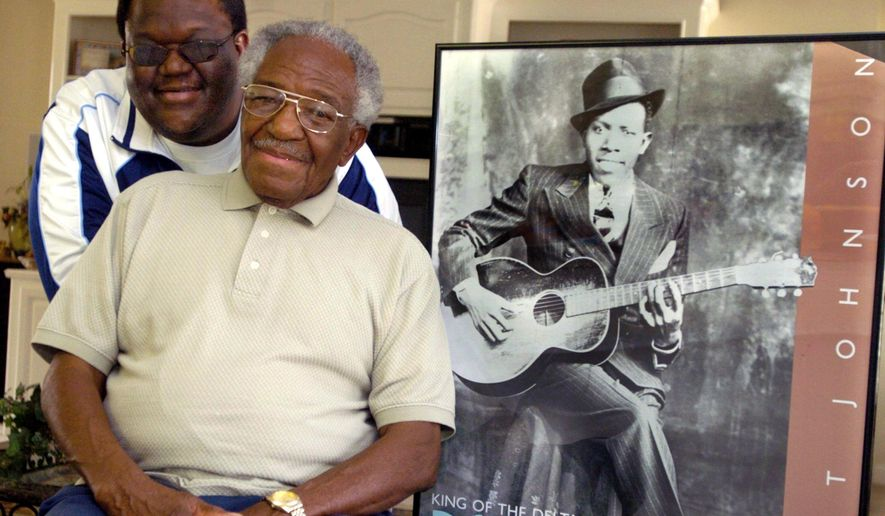 FILE - In this Feb. 1, 2006 file photo taken in Crystal Springs, Miss., Claud Johnson, seated, son of legendary Mississippi blues artist Robert Johnson, shown in the poster on the right, has died at age 83. Johnson who posed with his own son Michael Johnson, won a legal fight in 2014 to keep the profits from the only two known photographs of his father. (Greg Jenson/The Clarion-Ledger, via AP Photo)