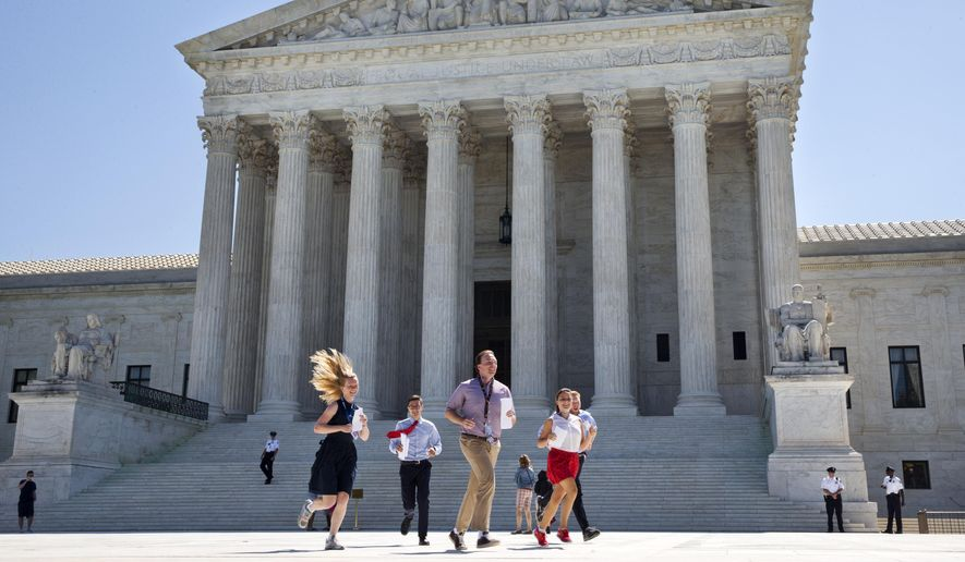 """New interns run with a decision across the plaza of the Supreme Court in Washington, Monday June 29, 2015. On Monday, the court upheld Arizona congressional districts drawn by an independent commission and rejected a constitutional challenge from Republican lawmakers and upheld the use of a controversial drug in lethal injection executions Monday, as two dissenting justices said for the first time that they think it's """"highly likely"""" that the death penalty itself is unconstitutional.  (AP Photo/Jacquelyn Martin)"""