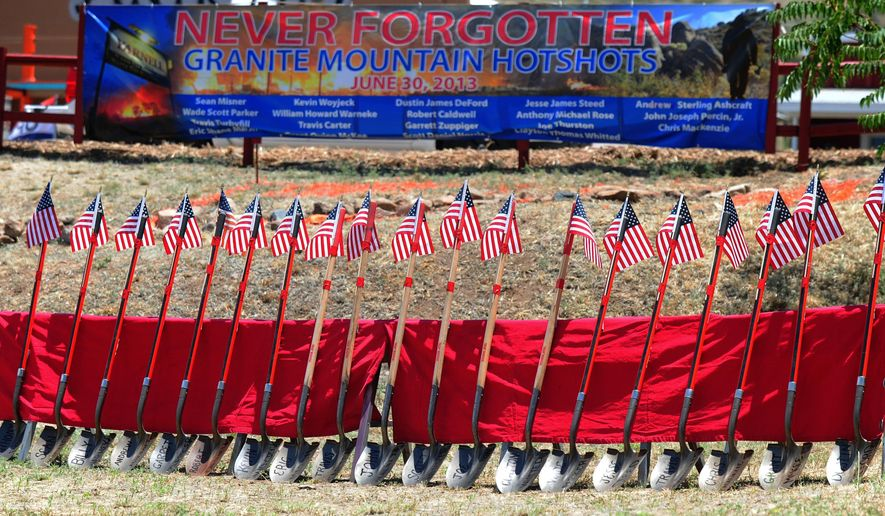 Flag-topped shovels with the names of the Granite Mountain Hotshots on their blade were a grim reminder of the loss of life that occurred two years ago as local residents gather Sunday June 28, 2015, for the Remembrance Event of the 2nd Anniversary of the Yarnell Hill Fire in Yarnell, Ariz. Nineteen firefighters, all but one member of the Prescott-based Granite Mountain Hotshots died when the men were overrun by flames in a brush-choked canyon near Yarnell. (Les Stukenberg/The Daily Courier via AP) MANDATORY CREDIT