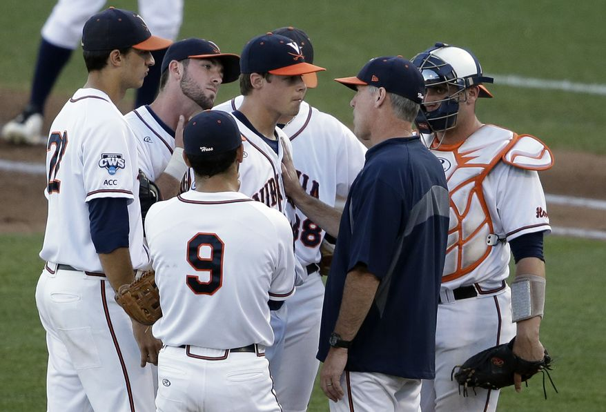 Virginia coach Brian O'Connor confers with pitcher Nathan Kirby in the third inning of one of the best-of-three games against Vanderbilt in the NCAA baseball College World Series finals in Omaha, Neb., Monday, June 23, 2014. (AP Photo/Nati Harnik)