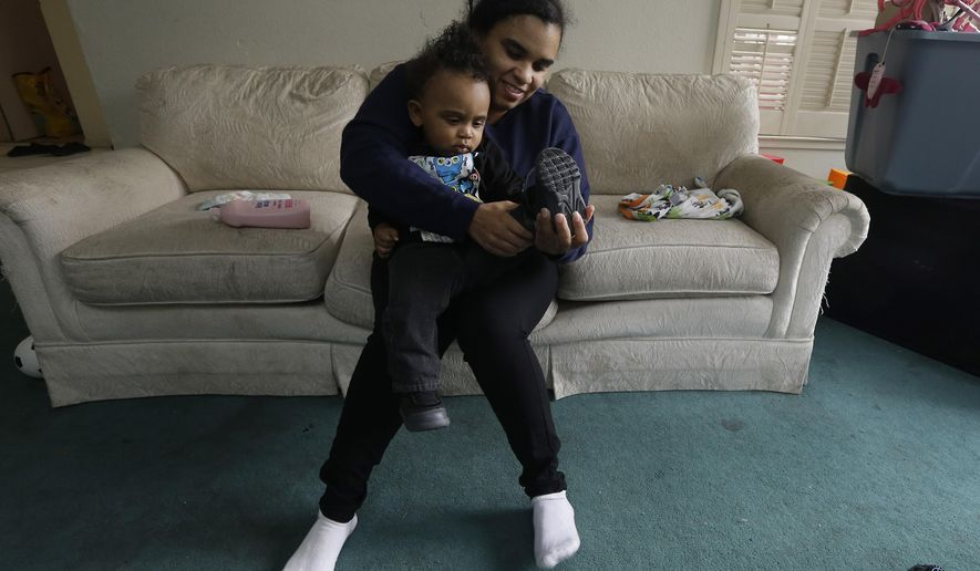 FILE - In this May 15, 2015 file photo, Shannon Henderson gets her son, Justin, 1, dressed before leaving for her job as a part- time customer service representative at a Walmart in Sacramento, Calif. Henderson is one of an estimated 40 million American workers that don't receive paid sick days. One of the new laws taking effect July 1 in California will require employers to provide at least three paid sick days each year. (AP Photo/Rich Pedroncelli,file)