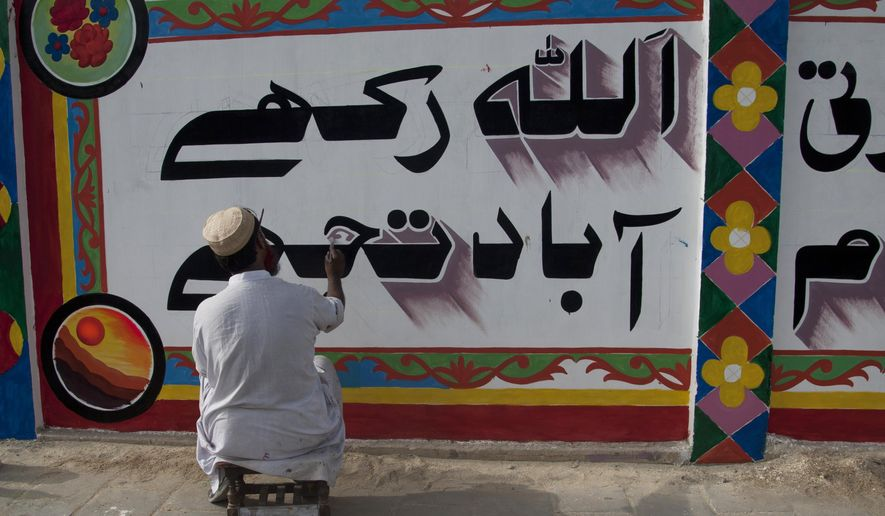 "In this photo taken Thursday, June 4, 2015, a Pakistani calligraphist paints, ""God bless you,"" in Urdu over violent graffiti on the wall of an apartment complex and offices after getting permission in Karachi, Pakistan. Activists and artists in Pakistan hope to combat extremism through art, by painting murals over violent graffitti and distributing a comic book in schools aimed at turning young people away from violence. (AP Photo/Shakil Adil)"