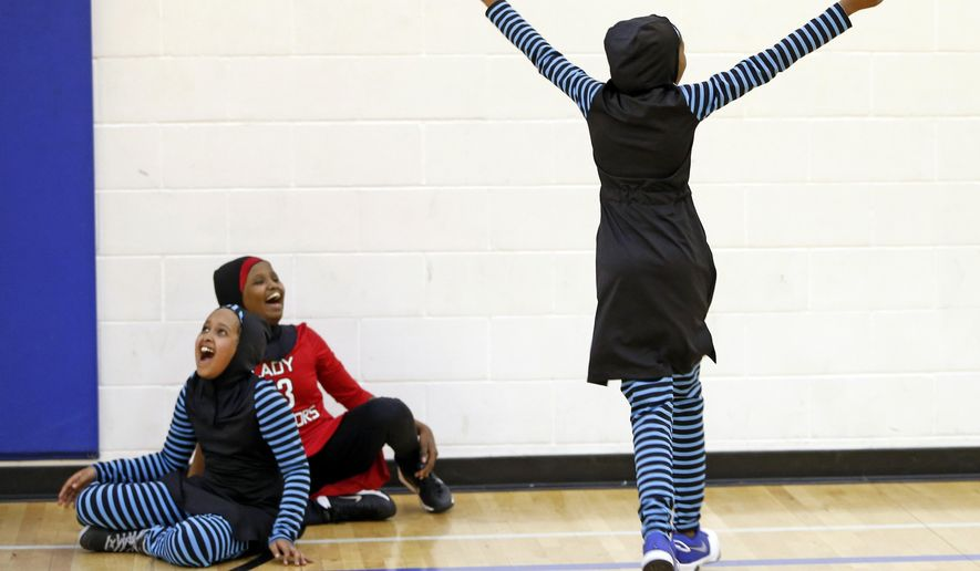 In this June 16, 2015, file photo, Ramla Ali, left, and Amira Ali, on Ramia's right, help celebrate a basket at an East African Muslim girls basketball practice in Minneapolis. Muslim girls who play sports have challenges that go beyond the sporting. Their new culturally sensitive uniforms, designed by the girls, address worries over tripping on a long, flowing dress, or having a loosely wrapped hijab come undone during a crucial play. (AP Photo/Jim Mone) ** FILE **