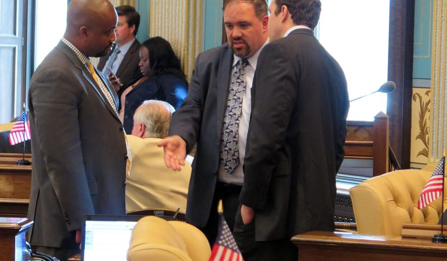 Sen. Minority Leader Jim Ananich, D-Flint, center, talks with Sen. Bert Johnson, D-Highland Park, left, and Darin Ackerman, Gov. Rick Snyder's deputy legislative affairs director, in the Michigan Senate chamber, Wedneday, July 1, 2015 in Lansing, Mich. The Republican-led Senate was deliberating Wednesday on a $1.5 billion plan to improve deteriorating Michigan roads by raising fuel taxes and redirecting money from elsewhere in the budget. (AP Photo/David Eggert)