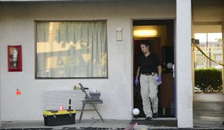 An Albuquerque Police Deptartment officer collects evidence Wednesday, July 1, 2015, after a man was killed and another injured during what police say was an altercation between the two late Tuesday at a Motel 6 in Albuquerque, N.M. A cross-country road trip got derailed for former CNN anchor Lynne Russell and her husband after a would-be robber forced his way into their motel room and a shootout ensued. (Adolphe Pierre-Louis/Albuquerque Journal via AP)