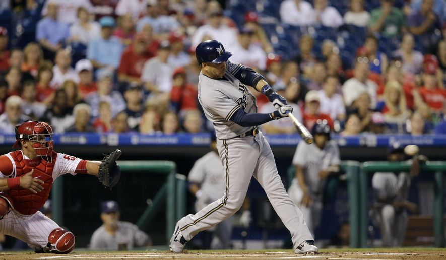 Milwaukee Brewers' Aramis Ramirez hits a two-run single off Philadelphia Phillies starting pitcher Cole Hamels as catcher Carlos Ruiz, left, watches during the first inning of a baseball game, Tuesday, June 30, 2015, in Philadelphia. (AP Photo/Matt Slocum)