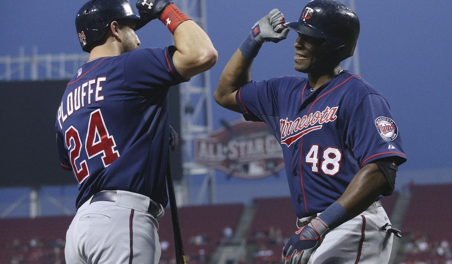 Minnesota Twins' Torii Hunter (48) celebrates with Trevor Plouffe (24) after hitting a solo home run off Cincinnati Reds starting pitcher Anthony DeSclafani in the first inning of a baseball game, Tuesday, June 30, 2015, in Cincinnati. (AP Photo/John Minchillo)