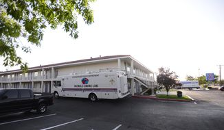 An Albuquerque Police Department Mobile Crime Lab is parked outside a Motel 6, Wednesday, July 1, 2015, where a man was found dead and another injured during what police say was an altercation between the two late Tuesday in Albuquerque, N.M. A cross-country road trip got derailed for former CNN anchor Lynne Russell and her husband after a would-be robber forced his way into their motel room and a shootout ensued. (Adolphe Pierre-Louis/Albuquerque Journal via AP)