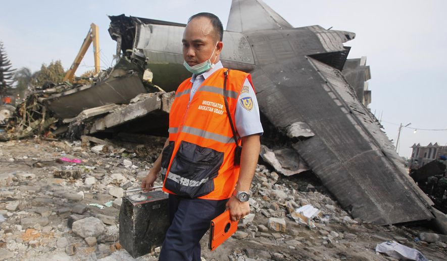 An investigator walks past the wreckage of the crashed air force transport plane in Medan, North Sumatra, Indonesia, Wednesday, July 1, 2015. The Hercules C-130 plane crashed into a residential neighborhood in the country's third-largest city on June 30. (AP Photo/Binsar Bakkara)