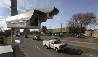 In this photo taken on Nov. 10, 2014, traffic along Keowee St. in Dayton, Ohio, flows past a photo enforcement traffic camera. Two more Ohio cities are challenging a state traffic camera law they say would restrict the cities' use of the cameras because it requires a police officer's presence to issue tickets, and they are asking the courts to find the law unconstitutional. Dayton and Springfield sued the state in their counties on Wednesday, March 18, 2015. (AP Photo/The Dayton Daily News, Lisa Powell )  LOCAL PRINT OUT; LOCAL TELEVISION OUT; WKEF-TV OUT; WRGT-TV OUT; WDTN-TV OUT