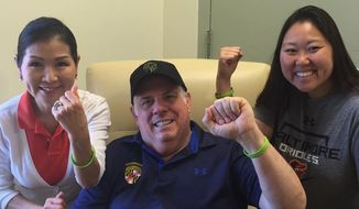 In this image released by the governor's office, Maryland Gov. Larry Hogan, center, is flanked by his wife Yumi, left, and daughter on Wednesday, July 1, 2015, at the University of Maryland Medical Center in Baltimore, Md., where he is being treated for B-cell non-Hodgkin lymphoma. (Christine Cascio/Maryland Governor's Office via AP)