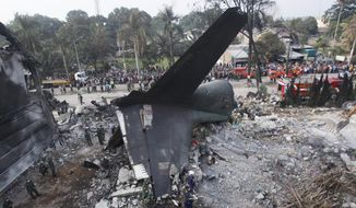 Rescuers search for victims at the site where an Indonesian air force transport plane crashed in Medan, North Sumatra, Indonesia, Wednesday, July 1, 2015. The Hercules C-130 plane crashed into a residential neighborhood in the country's third-largest city on June 30. (AP Photo/Binsar Bakkara)