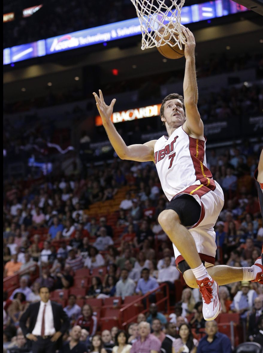 FILE - In this April 11, 2015, file photo, Miami Heat guard Goran Dragic (7) of Slovenia, goes up for a shot during the first half of an NBA basketball game against the Toronto Raptors in Miami. Dragic wasted little time in accepting a five-year, $90 million deal to remain with the Heat, the sides coming to an agreement in principle only a few hours after the NBA's free agency shopping period opened Wednesday, July 1, 2015. A person with knowledge of the negotiations confirmed the terms to The Associated Press on condition of anonymity because the deal cannot be finalized until July 9 per league rules. (AP Photo/Wilfredo Lee, File)
